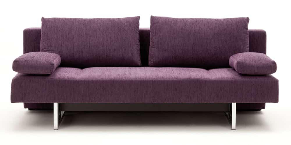 COIN Schlafsofa von Franz Fertig. Ideales Gästebett in lila. Sofa mit Schlaffunktion.
