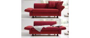 Schlafsofa MALOU von Franz Fertig mit Winkelbodenkissen und klappbaren Armlehnen. Fuß aus Holz. Sofa in rot mit Bettfunktion.