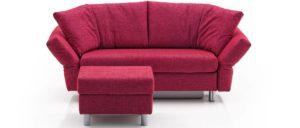 Schlafsofa MALOU von Franz Fertig mit dem MALOU Hocker. Klappbare Armlehnen, Winkelbodenkissen. Sofa in rot aber auch in schwarz, grau, braun. grün und weiteren Farben erhältlich.