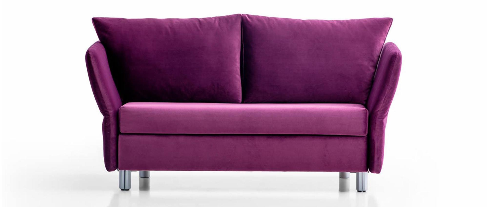 LUINO Schlafsofa von Franz Fertig mit klappbaren Armlehnen in lila. Sofa mit Gästebett Funktion. Sofa in lila.