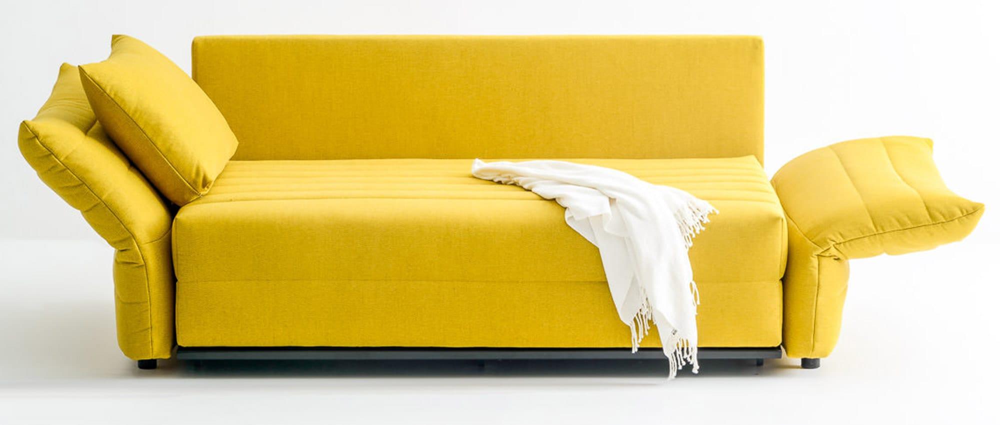 Schlafsofa ZERO von Franz Fertig mit klappbaren Armlehnen. Mit Rückenkissen und Vorstellkissen. Schlafsofa in gelb.